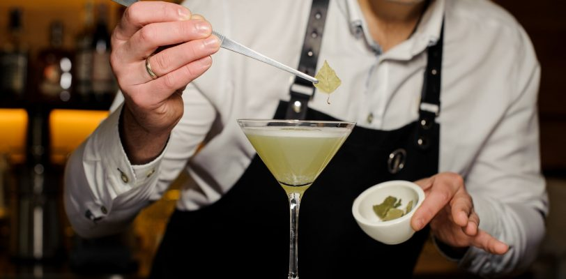 A mixology expert laying a leaf on a cocktail