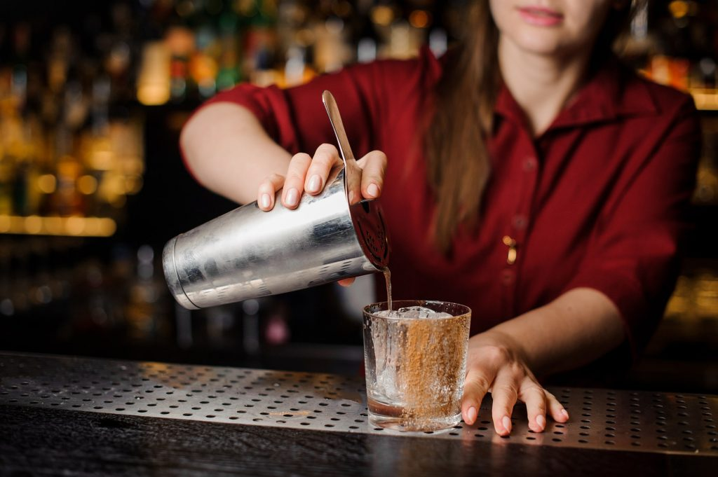 Bartender pouring liquid through a Hawthorne drink strainer