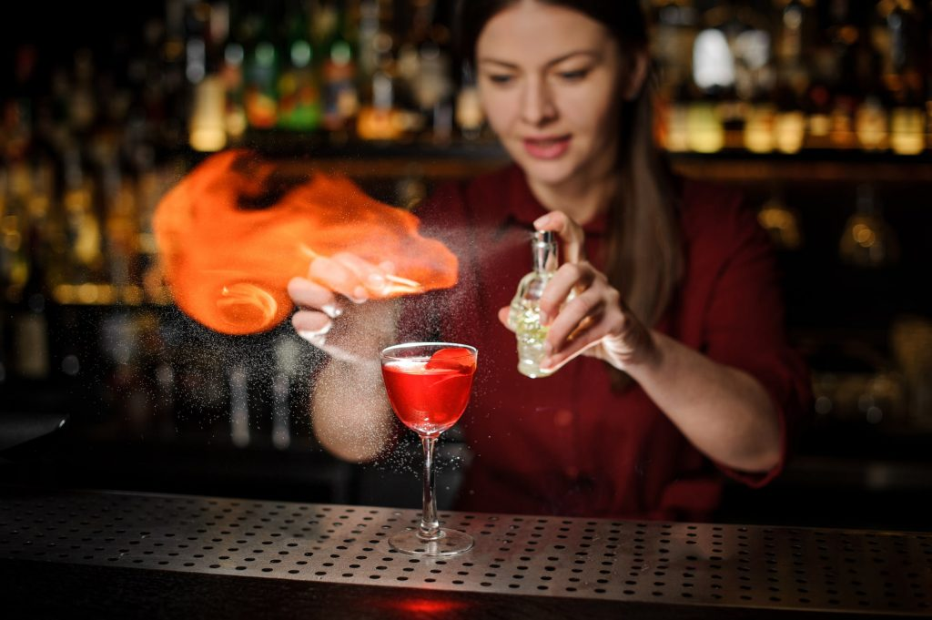 Female bartender showing off advanced cocktail making skills