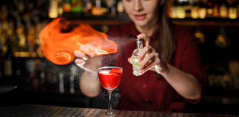 Female bartender showing off advanced cocktail making skills