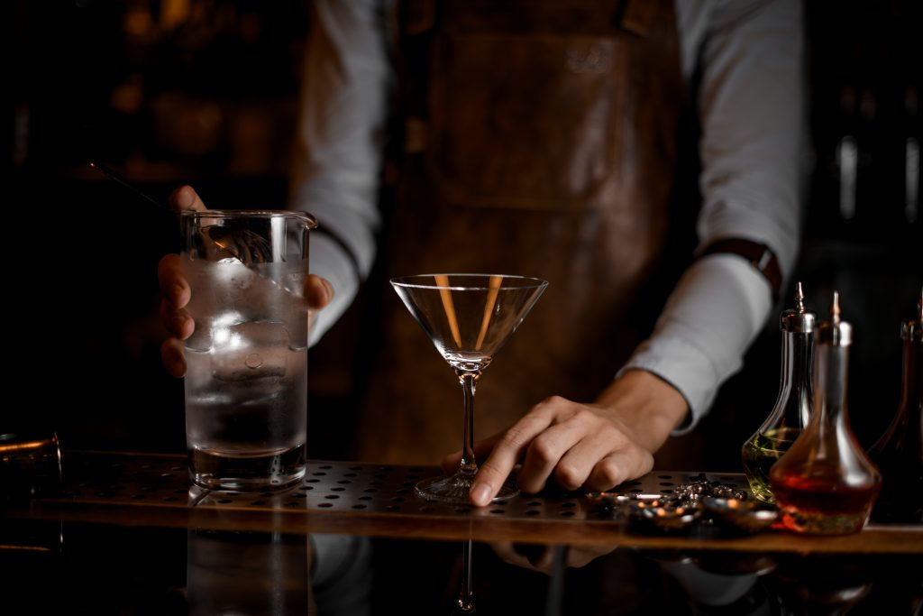 Male bartender prepares to pour a martini cocktail from jar with strainer